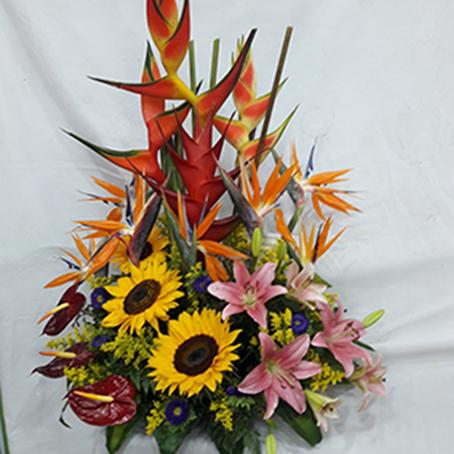 Diseño Triangular. 11 heliconias, 2 Girasoles, 4 Lirios, 3 Anturios, Algunas flores pueden variar según disponibilidad. 90.000$