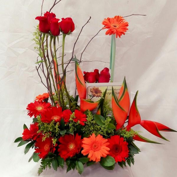 Diseño paralelo Transparente. 12 Rosas, 12 Gerberas, 2 heliconias, follaje y ojas de complemento. 80.000